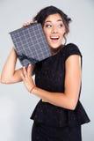 拿着礼物盒的黑礼服的可爱的妇女 免版税库存照片