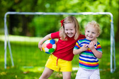 Дети играя футбол в парке Стоковое Изображение RF