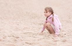 朝前看的小女孩下跪在沙子和 库存照片