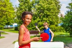 打与外面男孩的非洲女孩乒乓球 免版税库存图片