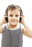 年轻男孩是微笑和听到音乐 免版税图库摄影