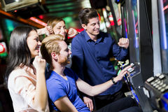 赌博在赌博娱乐场的朋友演奏槽孔和各种各样的机器 免版税库存照片