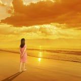 放松站立在海滩日落和山的妇女在假期旅行 图库摄影
