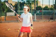 网球员、女运动员红土网球场的与球拍和球 与体育和实践概念的生活方式 图库摄影