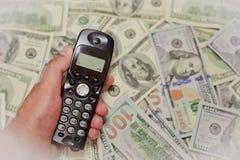 Рука держа телефон на деньгах, онлайн-банкинге Стоковые Фото