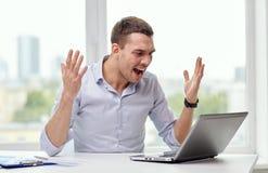 与膝上型计算机和纸的恼怒的商人在办公室 图库摄影