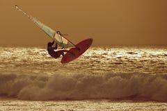 跳在日落天空的风帆冲浪者 免版税库存照片