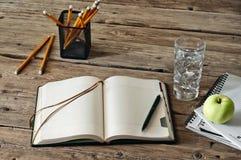 在木桌上的空白的日志与一杯水、苹果和铅笔特写镜头 免版税库存照片