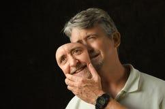 Человек биполярного расстройства подавленный с маской Стоковое Фото