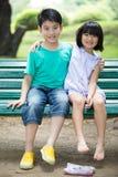亚裔逗人喜爱的男孩和小女孩是微笑和看照相机 免版税库存图片
