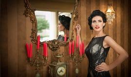 摆在葡萄酒场面的典雅的黑礼服的美丽的女孩 穿豪华礼服的年轻美丽的妇女 诱人的浅黑肤色的男人 图库摄影