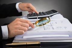 检查发货票的买卖人与放大镜 免版税库存图片