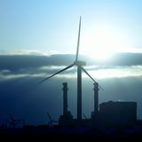 在电力设备和风轮机后的日出 免版税库存图片