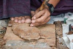 Профессия мастера в Мьянме, работая с деревянной статуей и высекая с инструментами внутри Стоковые Изображения RF