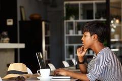 使用膝上型计算机的非裔美国人的妇女在咖啡馆 免版税库存图片
