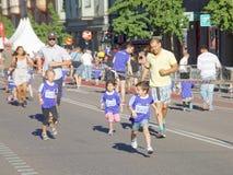 女孩、男孩和父亲赛跑 库存照片
