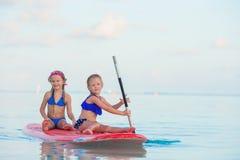 游泳在冲浪板的小逗人喜爱的女孩在期间 库存图片