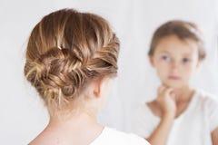 凝视她自己的孩子或女孩在镜子 免版税库存照片