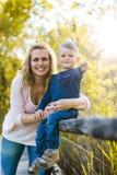 骄傲地举行她儿子和微笑的母亲 免版税库存照片