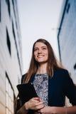 成功商人微笑,站立在大厦背景和拿着片剂计算机 城市女商人工作 图库摄影