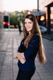 成功商人微笑,站立在大厦背景和拿着片剂计算机 城市女商人工作 库存照片