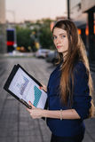 Успешный усмехаясь бизнесмен, стоя против фона зданий держа папку с диаграммами продаж Бизнес-леди города Стоковое Изображение RF