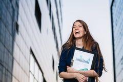成功的微笑的商人,站立反对拿着与销售图的大厦背景文件夹 城市女商人 免版税库存图片