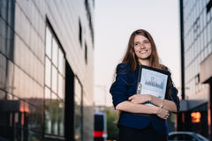 成功的微笑的商人,站立反对拿着与销售图的大厦背景文件夹 城市女商人 免版税库存照片
