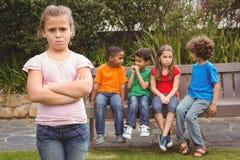 站立远离小组的生气孩子 库存图片