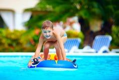 愉快的男孩,孩子获得乐趣在游泳池 库存图片