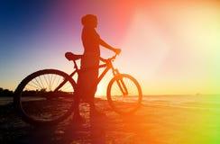骑自行车在日落的妇女 免版税库存照片