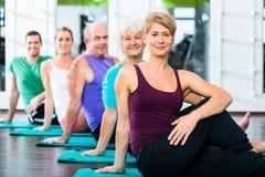 做在健身健身房的资深和青年人仰卧起坐 库存照片