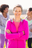 有胳膊的微笑的运动的妇女在朋友前面横渡了 免版税库存照片