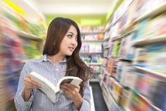 年轻亚洲妇女阅读书在图书馆里 库存照片