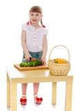 女孩切一个黄瓜 免版税库存照片