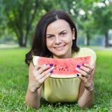 吃西瓜的微笑的少妇 免版税库存照片