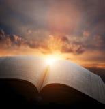 打开旧书,从日落天空的光,天堂 教育,宗教概念 免版税图库摄影
