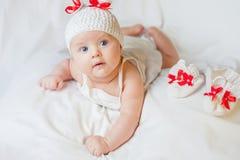 愉快的女婴在被编织的兔宝宝服装穿戴了 免版税图库摄影