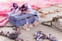 女性首饰和礼物盒在亚麻制桌布 免版税库存照片