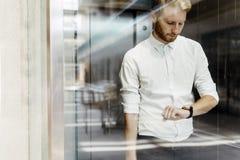 Бизнесмен проверяя вахту пока стоящ в лифте Стоковые Изображения RF