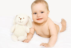 Χαριτωμένο μωρό με το παιχνίδι που βρίσκεται στο κρεβάτι Στοκ Φωτογραφία