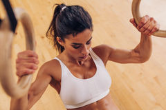 做引体向上的坚强的妇女使用体操圆环在健身房 免版税库存图片