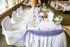 与花梢椅子的白色婚礼聚会桌和很多花、装饰、饮料和板材用食物 免版税图库摄影