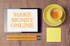 做金钱与数字式片剂和咖啡杯的网上概念 在视图之上 库存图片