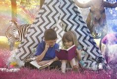 读动物幻想故事书的孩子 免版税库存照片