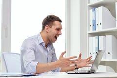 与膝上型计算机和纸的恼怒的商人在办公室 免版税库存图片