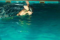 女子运动员游泳在水池的蝶泳 免版税库存照片