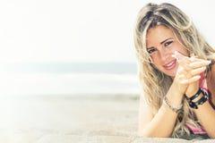 海上说谎在海滩的微笑的白肤金发的女孩 在早晨尘土拍的照片 免版税库存照片
