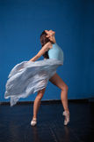 摆在蓝色的年轻现代跳芭蕾舞者 库存照片
