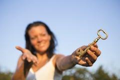 妇女金子钥匙手中蓝天 免版税库存图片
